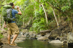 A male hiker refreshes with a drink of water while standing next to a river in a tropical jungle.